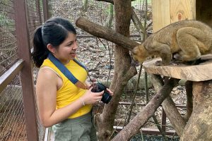 student Brianne Estrada wearing a camera around her neck, observes an animal in the Alturas sanctuary